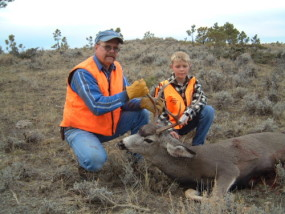 Dan's 4-point mule deer buck from 2002. Shot with a 250 grain .338 caliber Sierra Game King at about 400 yards. Adam helps drag him out.