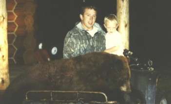 Rob Horton with his son Garrett with a big brown color phase black bear he shot in 1997.